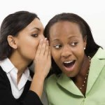 Two women whispering to each other