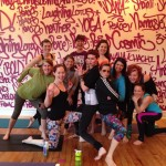 A group of yogis poses in front of graffiti